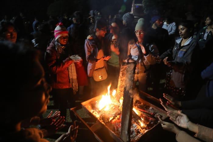 group of indian friends enjoying bonfire